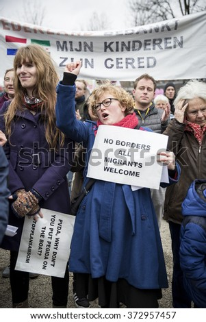 "Amsterdam, The Netherlands - February 6,2016: lady fist in the air at public multi-cultural demonstration organized to protest against racism and islamophobia named ""Refugees welcome, racism not!"""