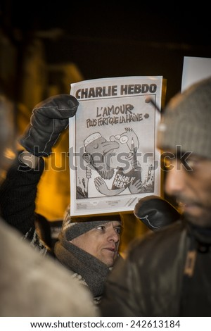 """Amsterdam, The Netherlands, January 08 2015: demonstation in solidarity with Charlie Hebdo in Paris, France on 07 January. A man holds an issue of Charlie Heddo where it says """"Love stronger than hate"""" - stock photo"""