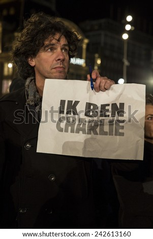 """Amsterdam, The Netherlands, January 08 2015: demonstation in solidarity with the attack against Charlie Hebdo in Paris, France on 07 January, man holding a sign saying """"I am Charlie"""" - stock photo"""