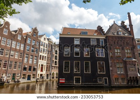 AMSTERDAM,THE NETHERLANDS - July 30, 2014: Houses on the banks of the canals of Amsterdam. Houses in Amsterdam are located directly on the water. Popular tourist attractions.