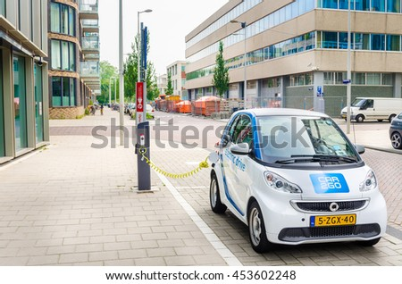 Amsterdam, The Netherlands - June 12, 2016: Car2Go Electric Car being Charged. Car2go is carsharing service available in Europe and North America. The Cars are user-accessed via a smartphone app - stock photo