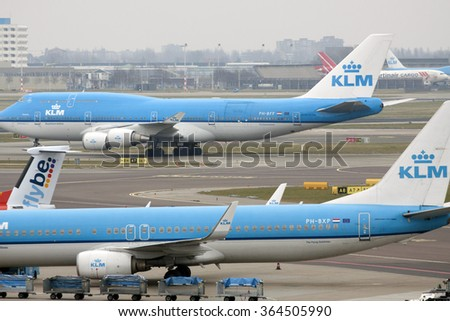 AMSTERDAM, THE NETHERLANDS - MAART 15, 2015: Moving beyond Boeing 747 cargo plane and in the foreground  a parked Boeing 737-900 KLM on maart 15 , 2015 in Amsterdam (Schiphol ), Holland.  - stock photo