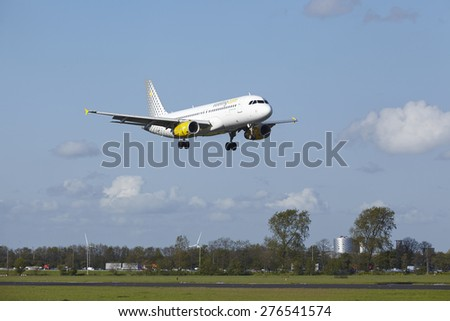 AMSTERDAM, THE NETHERLANDS - MAY, 7. An Airbus A320-232 of Vueling lands at Amsterdam Airport Schiphol (The Netherlands, AMS) on May 7, 2015. The name of the runway is Polderbaan.