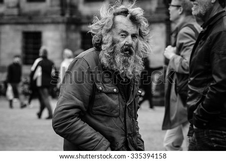 Amsterdam, The Netherlands - May 9, 2015: old poor  man walking by the streets of  Amsterdam on May 9, 2015 in Amsterdam, Holland - stock photo