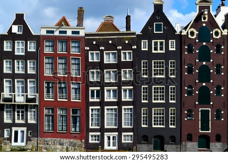 AMSTERDAM, THE NETHERLANDS - MAY 22. 2015: traditional buildings of Amsterdam city near the canal and boats