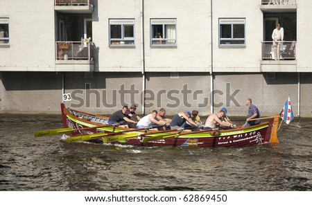 AMSTERDAM, THE NETHERLANDS - OCT 9: Rowing team from the town of Terherne participates in the annual 25 km long canal race, October 9, 2010 in Amsterdam, The Netherlands