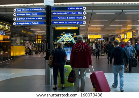 AMSTERDAM, THE NETHERLANDS - OCTOBER 4, 2013: Interior of Amsterdam Airport Schiphol. People using interactive map on October 4, 2013 in Amsterdam, Netherlands.