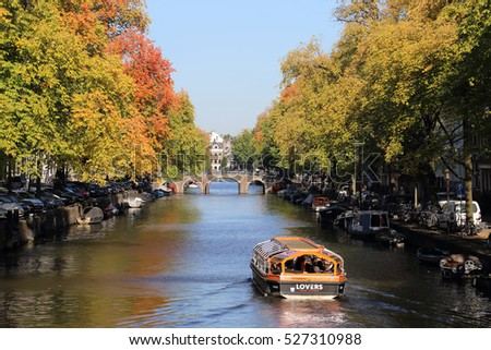 Amsterdam, The Netherlands - October 16, 2016: People sail in a tour boat on a canal with autumn trees in Amsterdam, The Netherlands on October 16, 2016