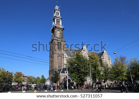 Amsterdam, The Netherlands - October 16, 2016: People walk in front of the famous Westerkerk church with autumn trees in Amsterdam, The Netherlands on October 16, 2016