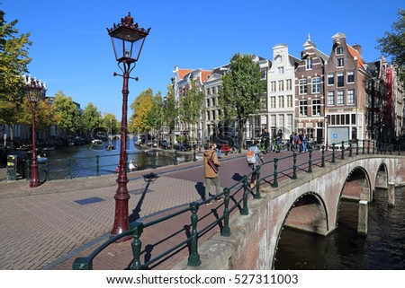 Amsterdam, The Netherlands - October 16, 2016: People walk on an old stone bridge in the historical part of Amsterdam, The Netherlands on October 16, 2016
