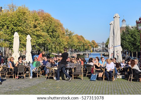 Amsterdam, The Netherlands - October 16, 2016: Waiter working and young people sit at a sidewalk cafe in the sun on a canal with autumn trees in Amsterdam, The Netherlands on October 16, 2016