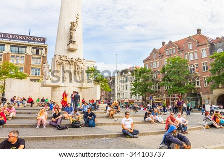 AMSTERDAM, THE NETHERLANDS - September 3, 2012: Tourists in the Dam square in Amsterdam, The Netherlands. The place is the historical center of the city and includes the Royal Palace.