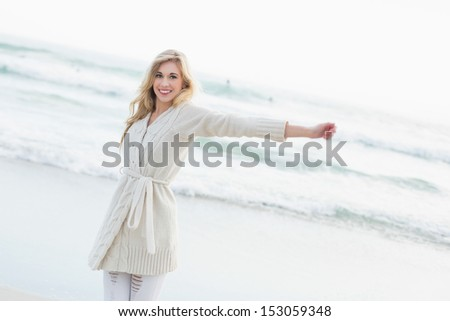 Amused blonde woman in wool cardigan stretching her arms on the beach - stock photo
