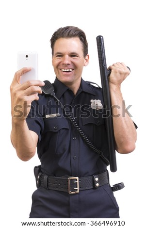 Amused Caucasian male police officer in uniform poses with baton while taking selfie photo with smart phone on white background - stock photo