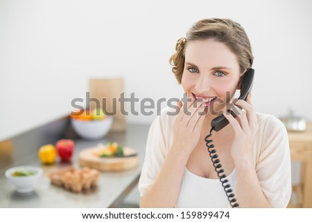 Amused lovely woman sitting in her kitchen phoning with a telephone looking at camera - stock photo