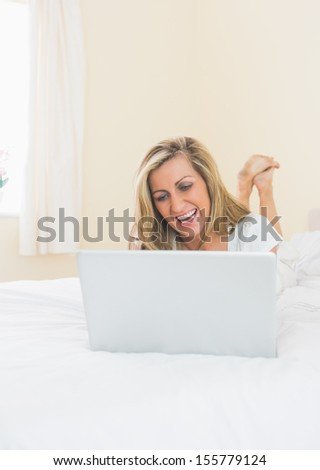 Amused mature blonde woman using a laptop lying on her bed in a bedroom