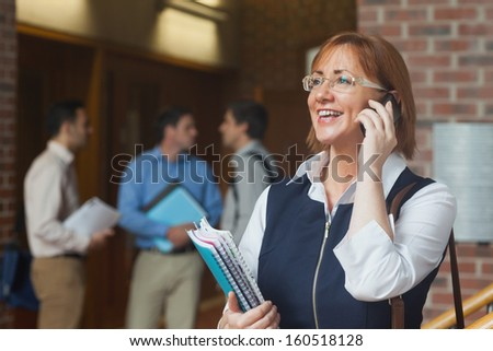 Amused mature student phoning standing in corridor holding some notebooks - stock photo