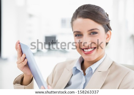 Amused smart brown haired businesswoman using a tablet pc in bright office