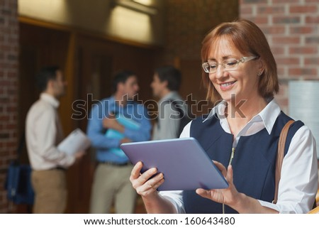 Amused smiling mature woman using her tablet standing with her classmates in a corridor - stock photo