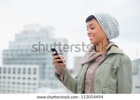Amused young model in winter clothes looking at her mobile phone outside on a cloudy day - stock photo
