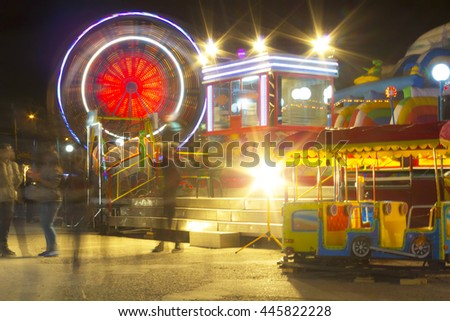 Amusement park at night - ferris wheel, carnival rides in action at night. - stock photo