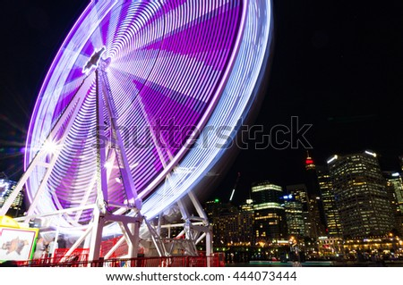 Amusement park attractions. Spinning ferris wheel at night with cityscape on the background. Motion blur - stock photo