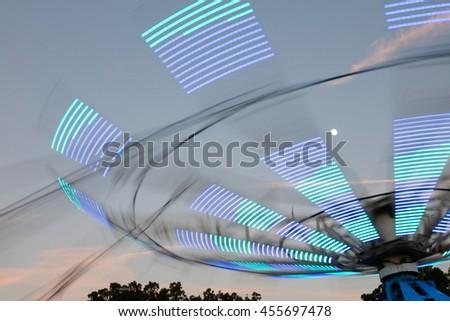 Amusement park ride at a county fair at dusk - stock photo