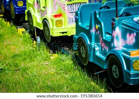 Amusement ride cars in a play park. Train of empty amusement cars, green grass and nobody around. Waiting for the kids - stock photo