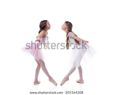 Amusing ballerinas posing looking at each other - stock photo