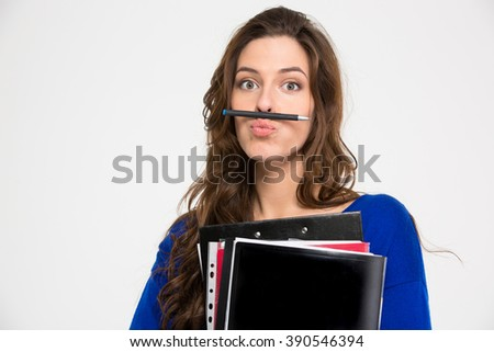 Amusing comical young woman holding folders and making funny face with pen over white background - stock photo