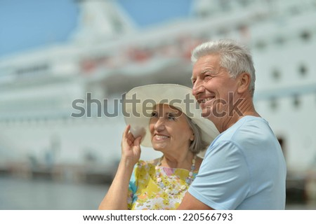 Amusing elderly couple against the background of the ship