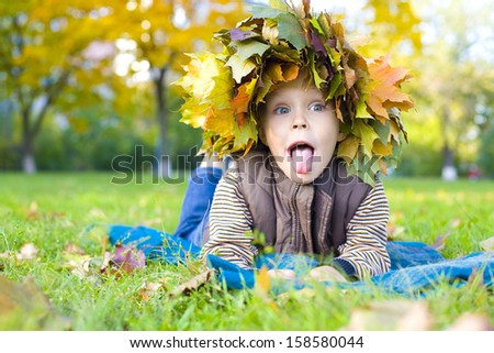 Amusing four-year-old boy in wreath from maple leaves lies on a grass and puts out tongue - stock photo