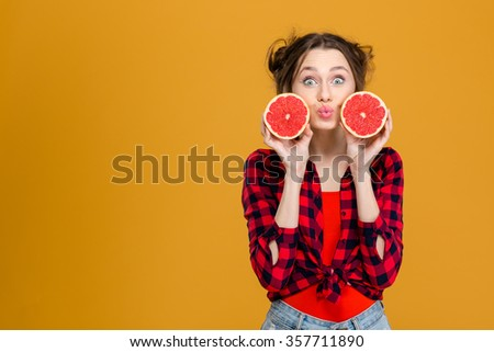 Amusing funny amazed young woman in checkered shirt making duck face and holding two halves of grapefruit over yellow background - stock photo