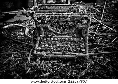 An abandoned and broken, antique, vintage typewriter, left outdoors with weeds and grass growing over it. In black and white.