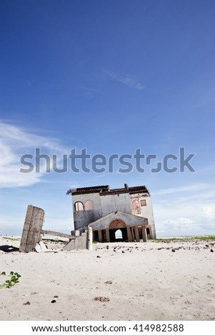 An abandoned and deserted house in the middle of nowhere in order to be demolished. - stock photo
