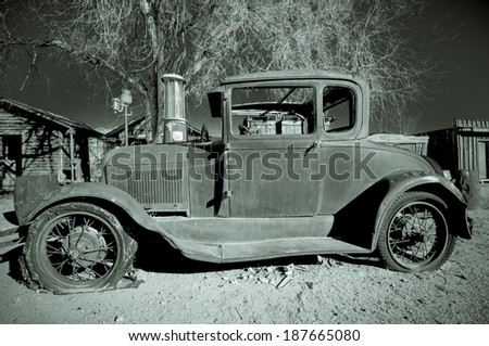 An abandoned car on a derelict site in the Eastern Sierras. - stock photo