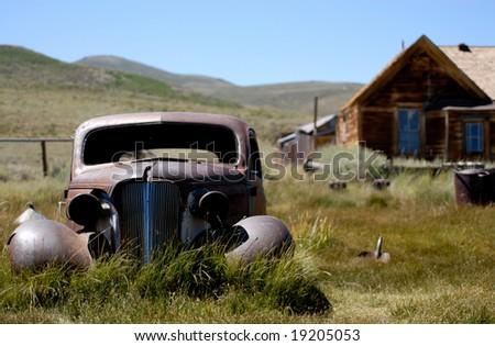 An abandoned car on the prairie - stock photo