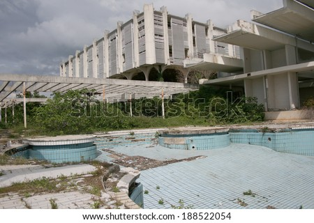 An abandoned five star hotel resort from 1970's with swimming pool decaying, poor management and finacial crisis - stock photo