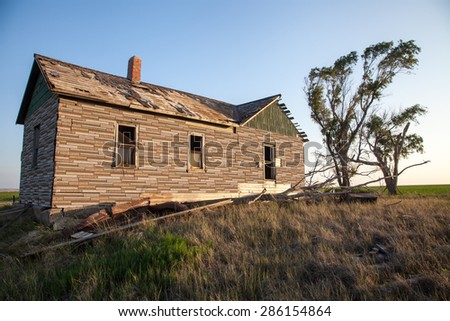 An abandoned homestead deteriorates over time in an open prairie - stock photo