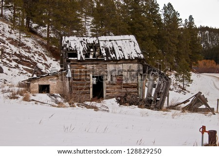 An abandoned homestead sits on a snowy hillside in the mountains of Montana