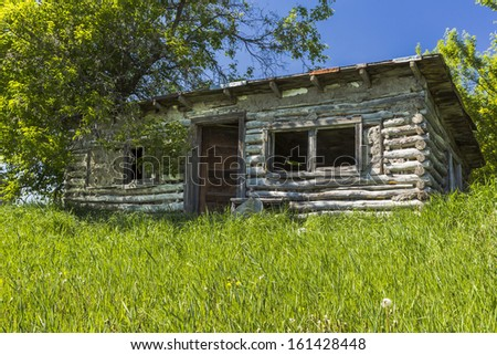 An abandoned log house in a small ghost town. - stock photo