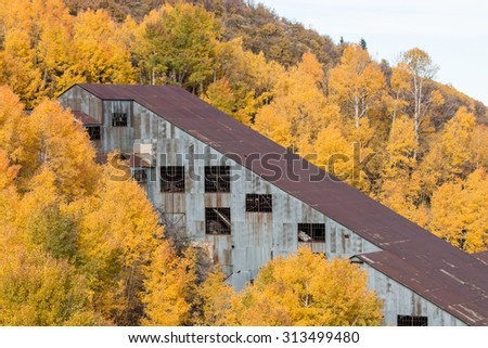 An abandoned mine sits among an aspen grove with fall colors - stock photo