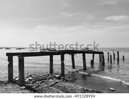 An abandoned pier at the lake in Black and White