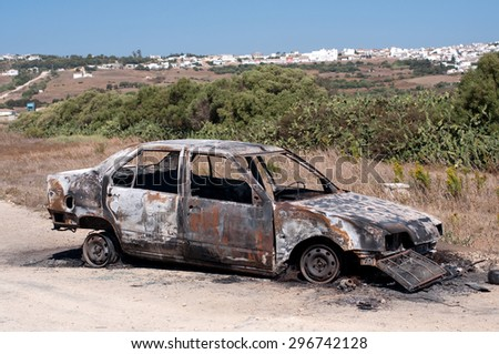 An abandoned, stolen burnt out car - stock photo