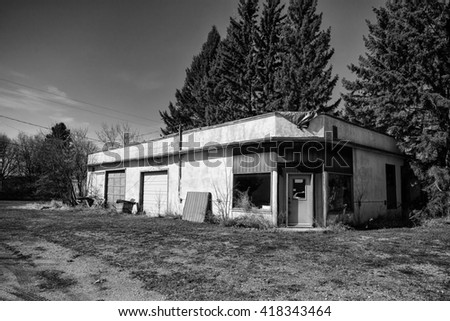 An abandoned stucco garage with two bay doors and junk laying around in black and white