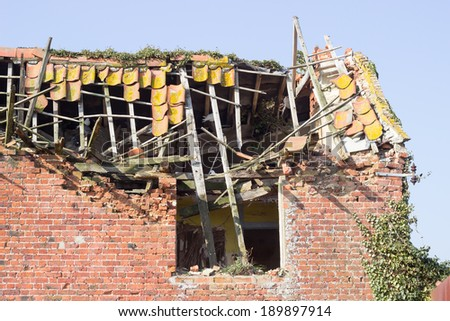 An abandoned tumbledown house, in a rural area. - stock photo