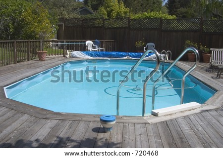 "An above ground ""Doughboy"" swimming pool surrounded by decking."