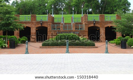 An above-ground (open) and underground (enclosed) parking garage in the side of a small hill in Yorktown Virginia. - stock photo