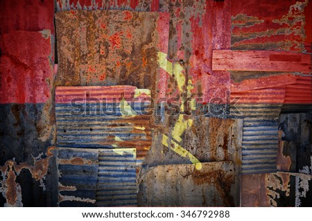 An abstract background image of the flag of Angola painted on to rusty corrugated iron sheets overlapping to form a wall or fence. - stock photo