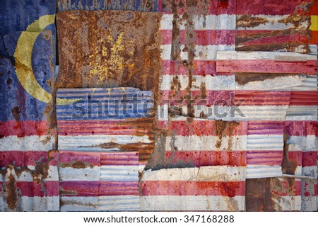 An abstract background image of the flag of Malaysia painted on to rusty corrugated iron sheets overlapping to form a wall or fence. - stock photo